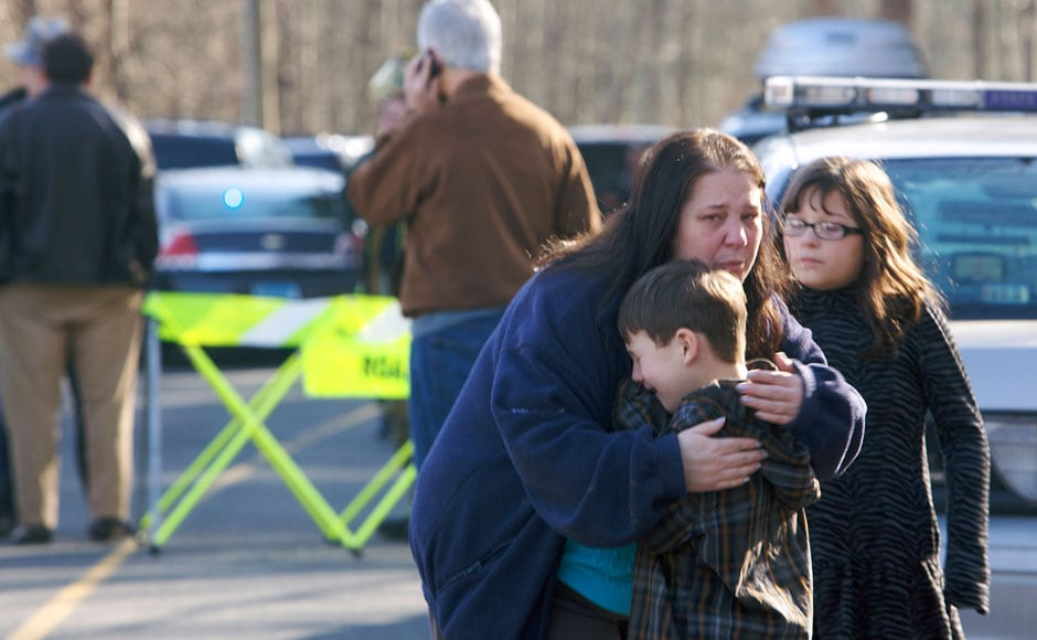 A young boy is comforted after the tragic shootout in the elementary school in Connecticut in which 27 people, including 18 children, were killed. Reuters.