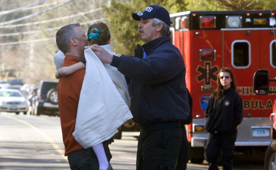 A young girl is handed over to her parent by a rescue operation worker after the shootout in the Sandy Hook Elementary School in Newtown, Connecticut, northeast of New York City. Reuters.