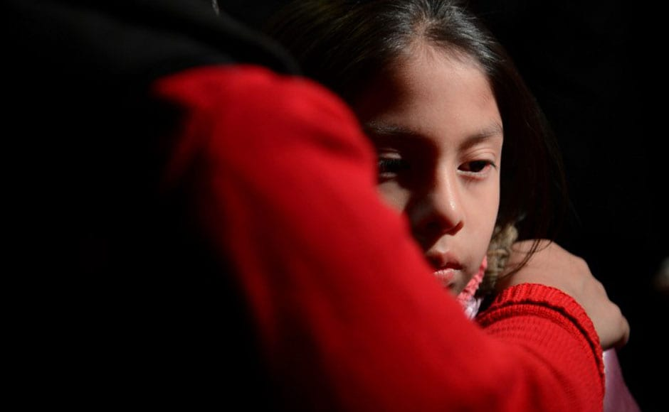 A girl is being comforted by her parents during a memorial service that was organised in the St Rose Church following the shooting in an elementary school in Newtown, Connecticut. AFP