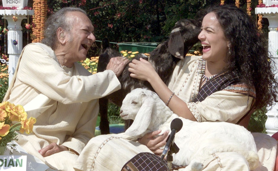 Indian sitar maestro Pundit Ravi Shankar laughs with his daughter sitar player Anoushka Shankar as they sit beside sheep in New Delhi February 25, 2002. The two artists were promoting an end to cruelty towards animals. Reuters
