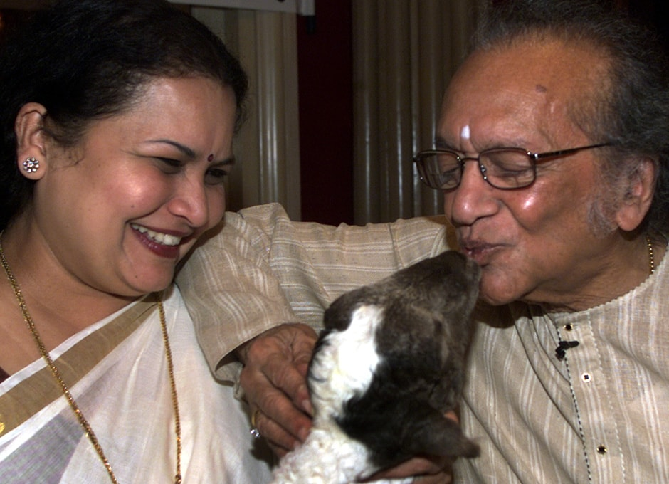 Sitar maestro Ravi Shankar (R) kisses Masoom, a two-and-a-half month old goat rescued from an abattoir, as his wife Sukanya Shankar looks on during a news conference in Bombay April 1, 2004. Reuters