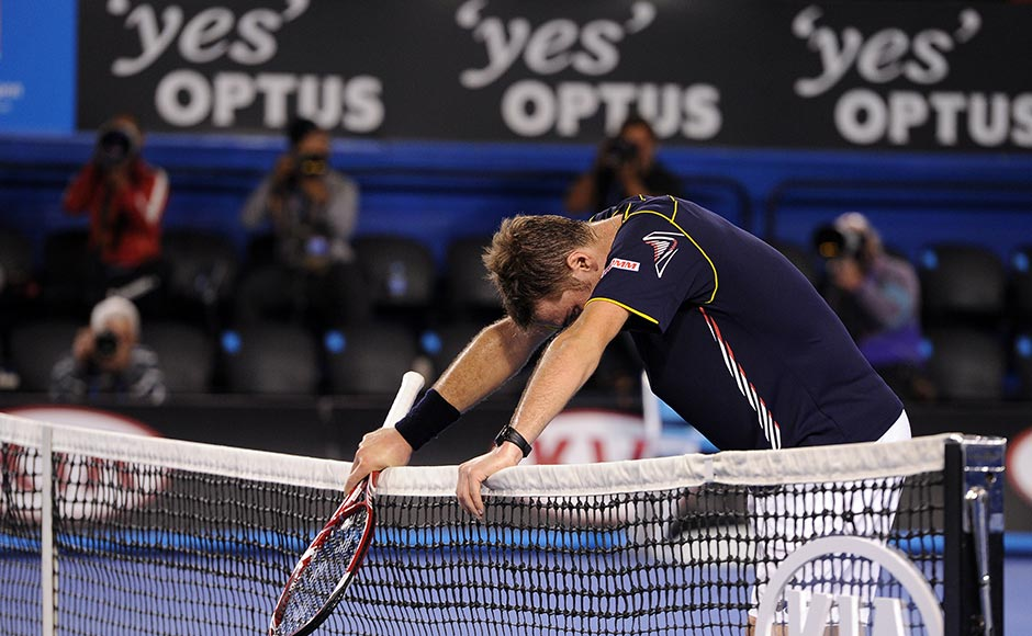 Switzerland's Stanislas Wawrinka rests on the net after losing his fourth round match against Serbia's Novak Djokovic at the Australian Open tennis championship in Melbourne. Andrew Brownbill/AP