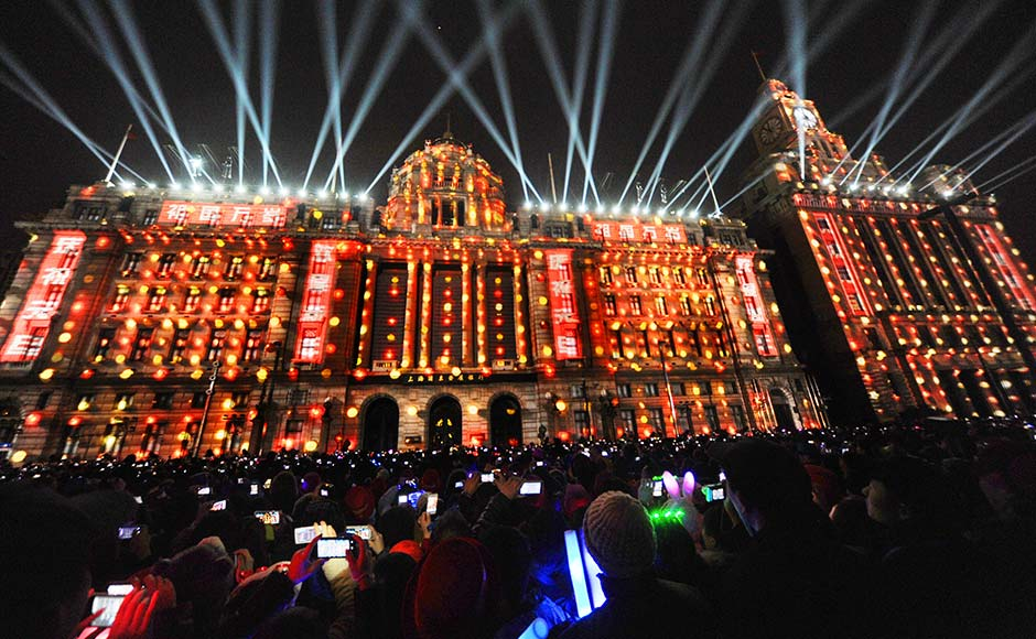 Visitors take pictures and videos during a light show as part of a New Year countdown celebration at the financial square on the Bund in Shanghai .Reuters