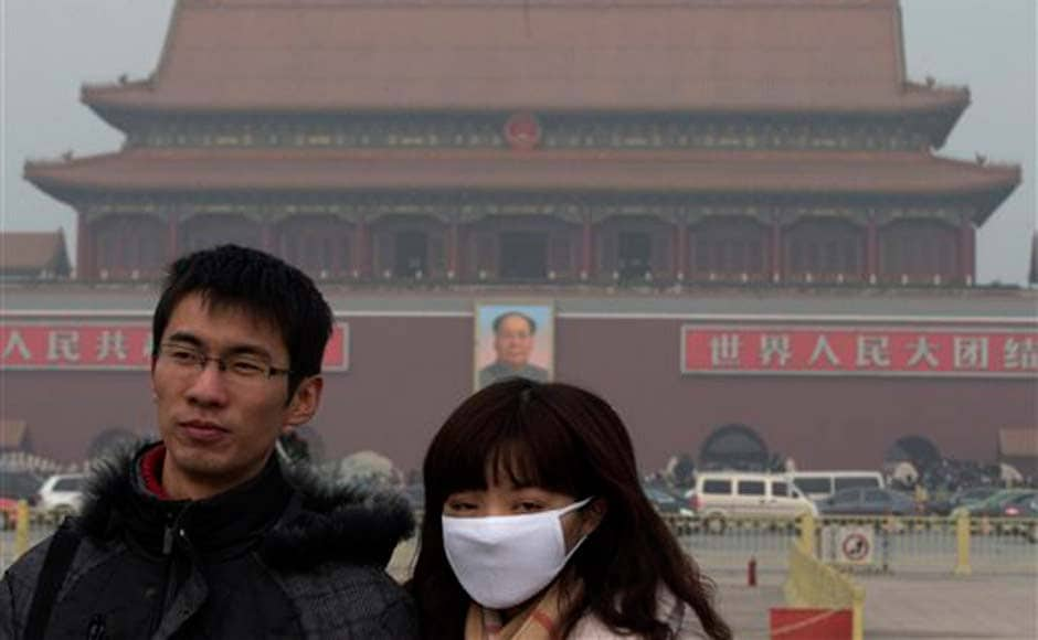 A woman wears a mask as she visits Tiananmen Square in Beijing: AP