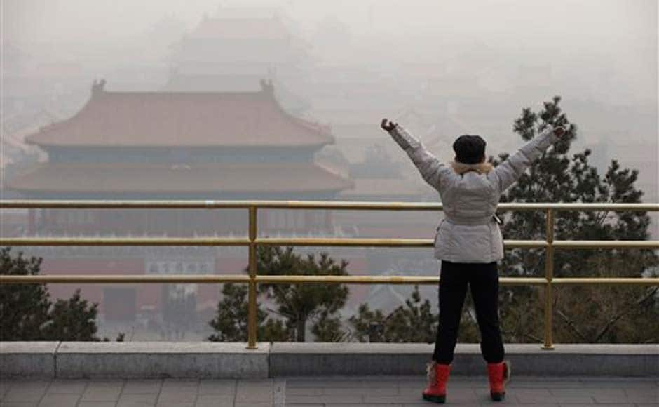 A visitor stretches her arms as she looks over the Forbidden City through severe haze in Beijing: AP