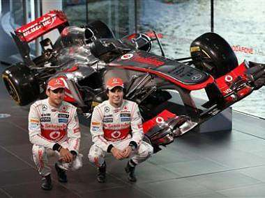 McLaren Formula One drivers Jenson Button and Sergio Perez pose at the unveiling of the McLaren MP4-28 at the company's headquarters in Woking. Reuters