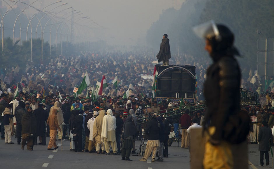 A police officer stands guard while supporters of Tahir-ul-Qadri participate in an anti government rally in Islamabad on Tuesday. AP