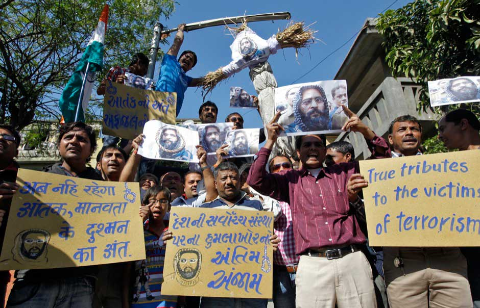 Demonstrators carry placards and posters and an effigy depicting Mohammad Afzal Guru during celebrations in the western Indian city of Ahmedabad today.Reuters