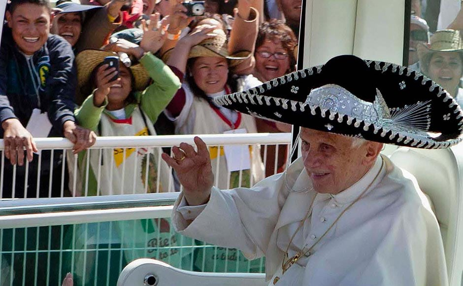In this March 25, 2012 file photo, Pope Benedict XVI waves from the Pope-mobile wearing a Mexican sombrero as he arrives to give a Mass in Bicentennial Park near Silao, Mexico. Eduardo Verdugo/AP