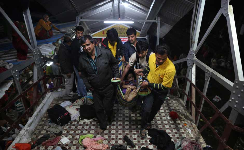 Volunteers take away a person injured in the stampede at the Allahabad station. AP