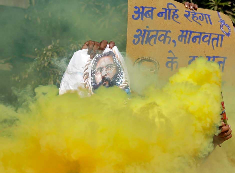 A demonstrator holds a poster of Mohammad Afzal Guru as another releases coloured smoke during celebrations in the western Indian city of Ahmedabad today.Reuters