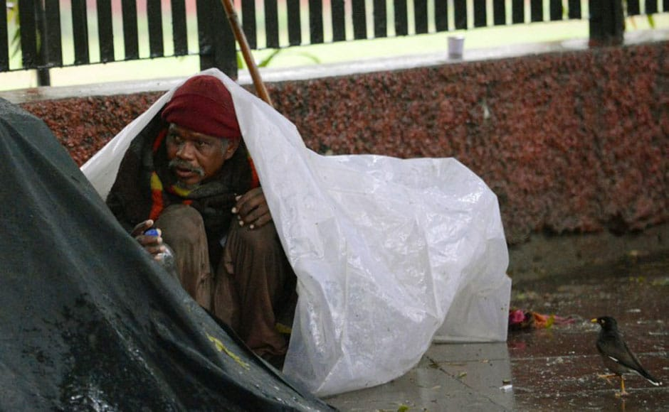 A homeless man takes shelter under a tarpaulin sheet. AFP