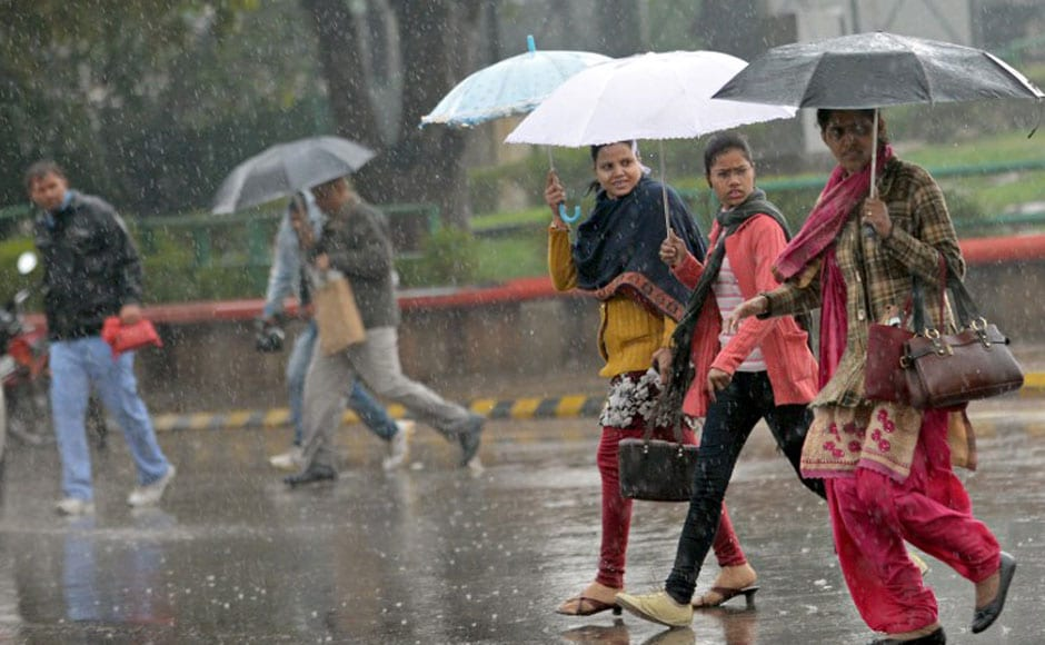 Pedestrians cross a road as it rains in Delhi on Tuesday. AFP