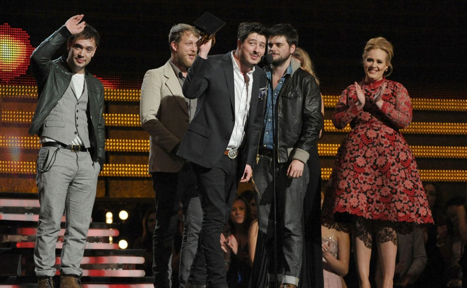 Mumford & Sons accept the award for album of the year for Babel as presenter Adele looks on. AP