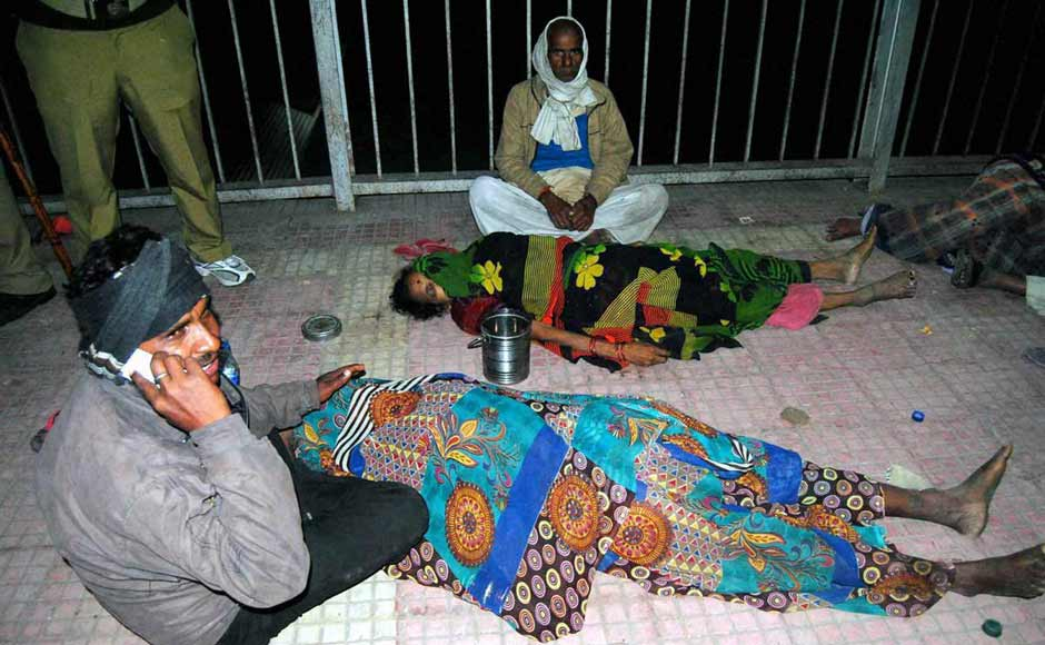Relatives of victims of the stampede sit next to bodies at the Allahabad station. PTI