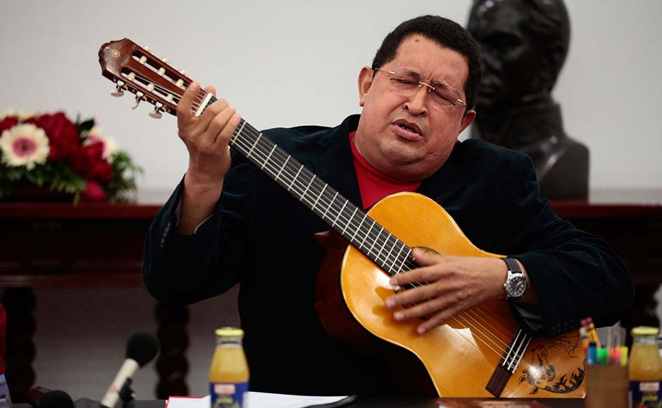 Venezuelan President Hugo Chavez plays a guitar, which was a gift from Mexican singer Vicente Fernandez, during a cabinet meeting at Miraflores Palace in Caracas September 20, 2012. Miraflores Palace/Reuters