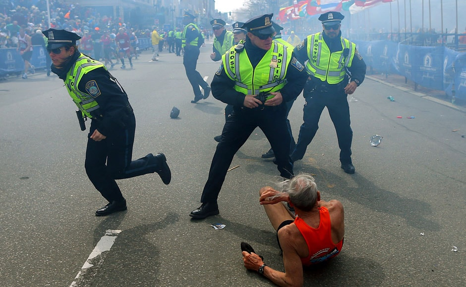 Bill Iffrig, 78, lies on the ground as police officers react to a second explosion at the finish line of the Boston Marathon in Boston, Monday, April 15, 2013. Iffrig, of Lake Stevens, Wash., was running his third Boston Marathon and near the finish line when he was knocked down by one of two bomb blasts. AP Photo/The Boston Globe, John Tlumacki