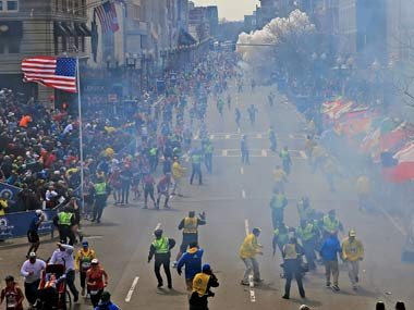 People react as a bomb goes off during the Boston Marathon. AP