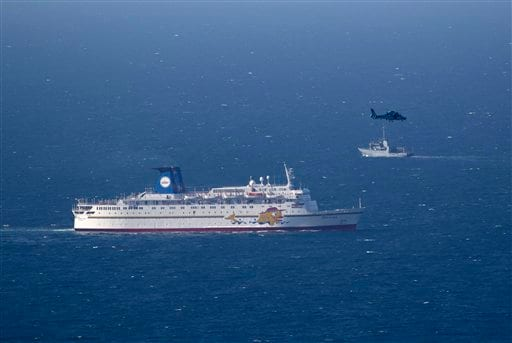 An Israeli military naval ship and an Israeli air force helicopter operate next to a cruise ship off the coast of Haifa. AP