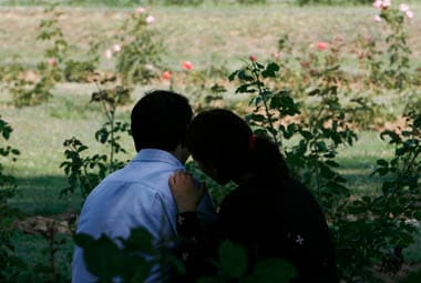 A Kashmiri couple sits together under the shade of a tree in a garden in Srinagar