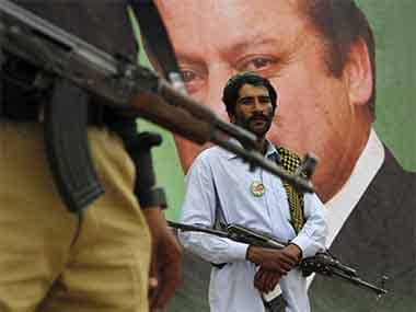 A policeman and a private guard stand near the portrait of Nawaz Sharif, leader of political party Pakistan Muslim League-Nawaz (PML-N), during an election campaign rally in Peshawar May 7, Reuters