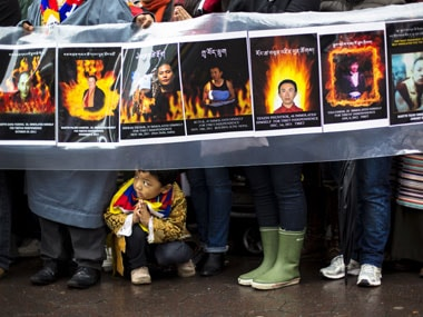 A child gestures at the feet of protesters holding a sign commemorating victims of self-immolation during a solidarity march in New York. Reuters