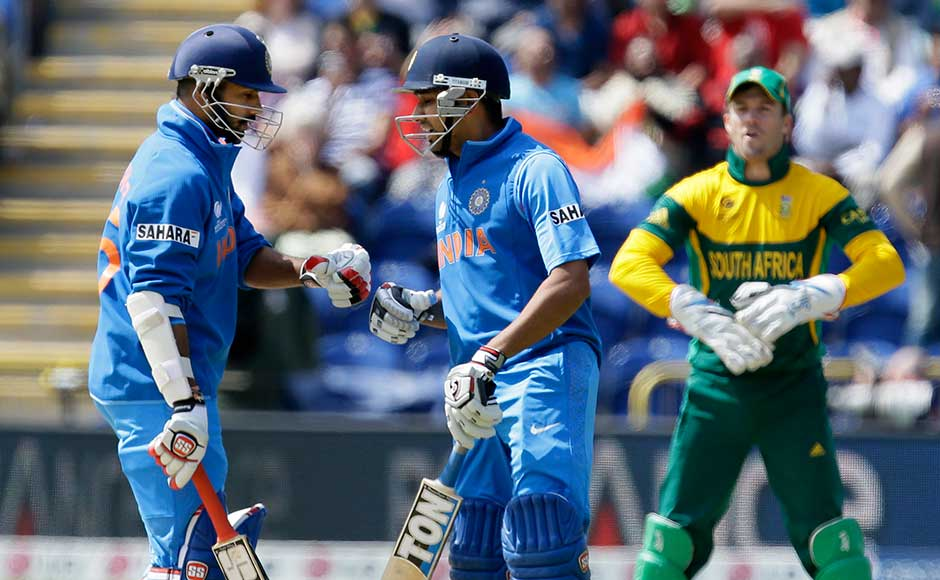 Rohit Sharma, right, and teammate Shikhar Dhawan tap gloves in the middle of the pitch as they play against South Africa during their group stage ICC Champions Trophy cricket match in Cardiff, Wales. Alastair Grant/Associated Press