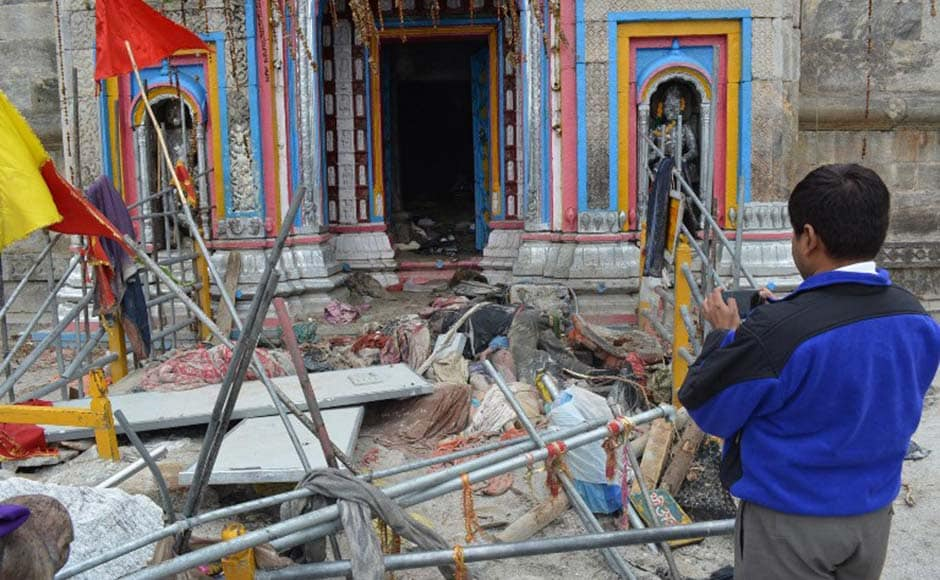 In this photograph taken on June 20, 2013, a bystander takes photographs of bodies and debris at the flash-flood hit Kedarnath Temple in Kedarnath. AFP