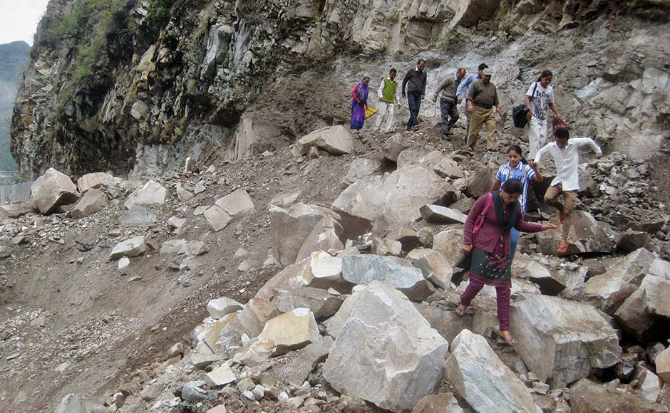 People walk on a mountain near a highway damaged by a landslide in Chamoli district, in Uttarakhand. AP