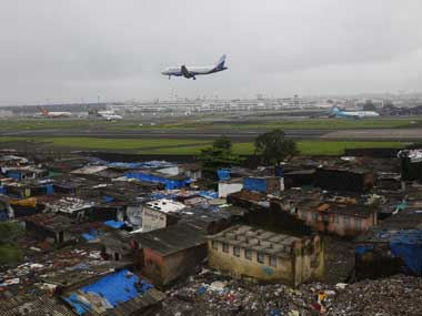 An aircraft prepares to land at the airport surrounded by slums in Mumbai. Reuters