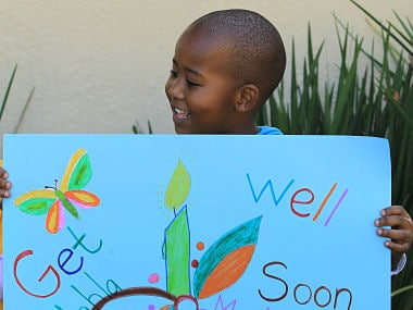 A young boy from Othandweni Community Center holds a placard wishing former South African President Nelson Mandela a prompt recovery. AP