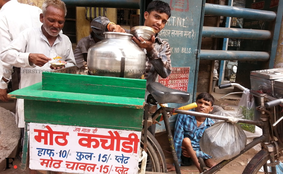 Eighteen year old Vikas Kumar from Faizapur in UP, has been selling 'moth' dal and kachori in Chawdi Bazaar, on his cycle since the past five months. He sells half plate of 'moth' dal and kachori for Rs. 10 and a full plate for Rs. 15. Arlene Chang/Firstpost.