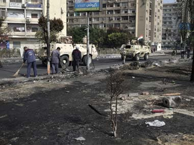Egyptian government employees clean up as members of the Egyptians Army patrol among the smoldering remains of the largest protest camp of supporters of ousted President Mohammed Morsi. AP