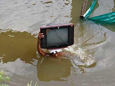 File photo of man carrying his television after floods in his village. Reuters