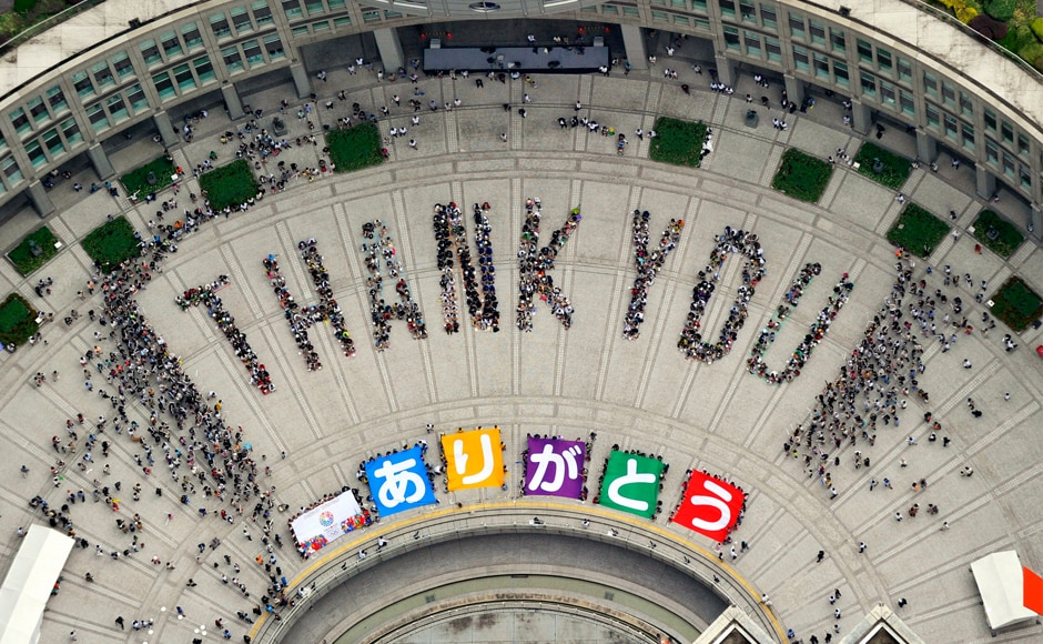 "An aerial view shows people sitting in formation to the words ""thank you"" and displaying signs that collectively read ""Arigato"" (Thank You) during an event celebrating Tokyo being chosen to host the 2020 Olympic Games, at Tokyo Metropolitan Government Building. Reuters."