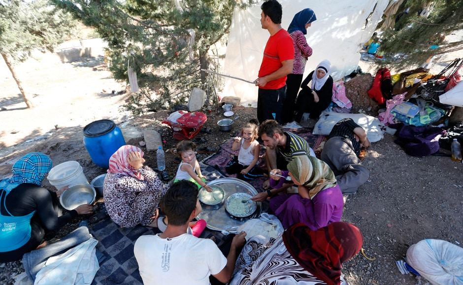 Syrian refugees, who failed to find shelters in a refugee camp, eat and rest by the roadside, a few meters away from the Oncupinar border crossing on the Turkish-Syrian border: Reuters