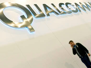 A man walks past a Qualcomm advertising logo at the Mobile World Congress at Barcelona, February 27, 2013. The GSMA Mobile World Congress, representing the interests of the worldwide mobile communications industry, takes place from February 25 to 28 in Barcelona. Reuters