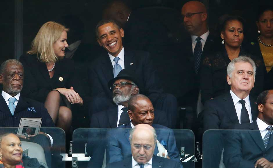 President Barack Obama jokes with Danish Prime Minister Helle Thorning-Schmidt, left, as US first lady Michelle Obama looks on during the memorial service for former South African president Nelson Mandela at the FNB Stadium in Soweto, near Johannesburg, South Africa. AP