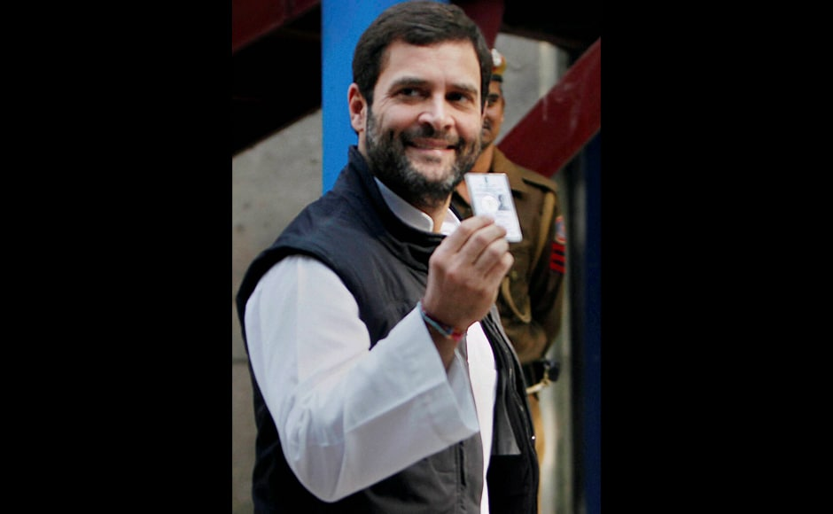 Congress Vice President Rahul Gandhi shows his voter identity card as he leaves after casting his vote in the Delhi Assembly elections at a polling station in New Delhi on Wednesday. PTI