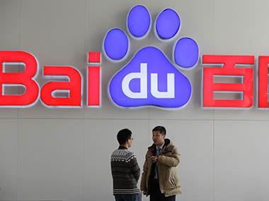 People talk in front of a Baidu's company logo at Baidu's headquarters. Reuters