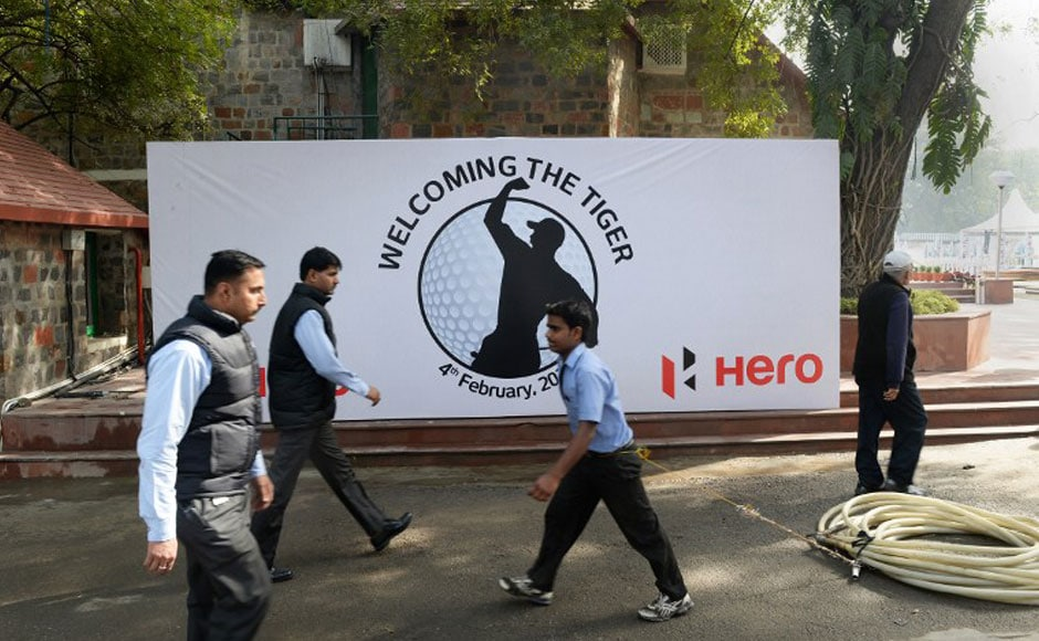 Workers arrange signs featuring images of US golfer Tiger Woods at The Delhi Golf Club in New Delhi. AFP