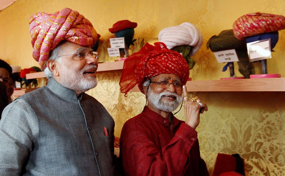 Gujarat Chief Minister and BJP's PM candidate Narendra Modi wears a traditional Gujarati turban at a stall during inauguration of five-day long handicraft exhibition in Ahmedabad on Friday. PTI