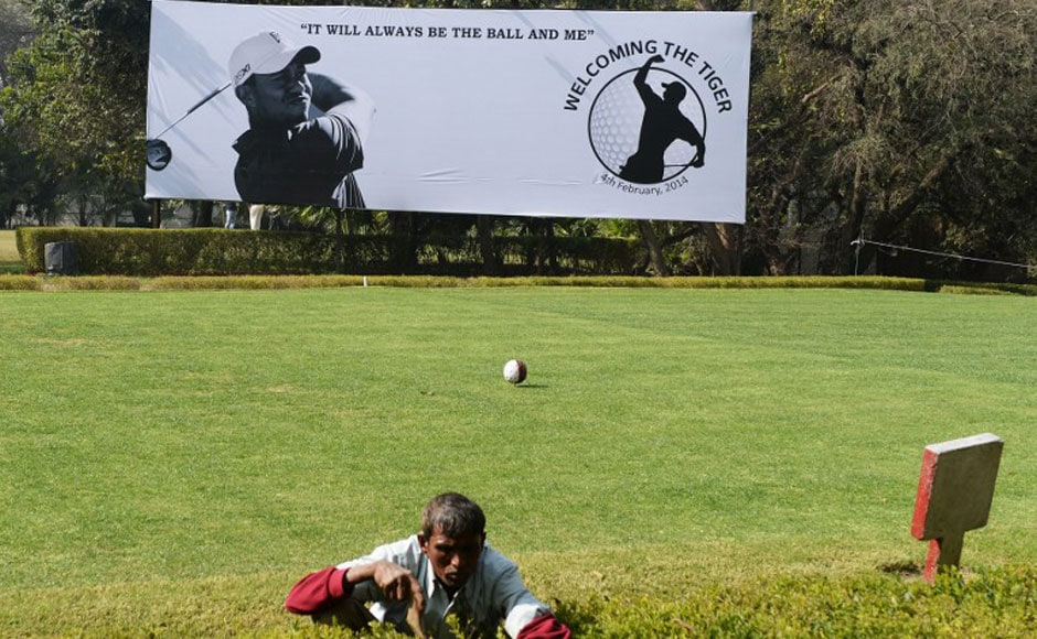 A gardener works on a hedge in front of a billboard featuring images of US golfer Tiger Woods at The Delhi Golf Club in New Delhi. AFP