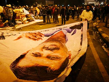 A supporter of Aam Aadmi (Common Man) Party (AAP) removes a poster with a portrait of Delhi CM Kejriwal from the site of a protest after Kejriwal called off the sit-in protest against the police in New Delhi. Reuters
