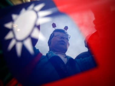 A supporter of Taiwan President and KMT presidential candidate Ma Ying-jeou ic pictured through a Taiwan flag during a campaign rally for the 2012 presidential election in Taipei
