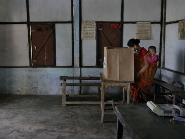 A Mishing tribal woman with her baby casts her vote inside a polling center as a securityman stands guard during the first phase of elections at Misamora Sapori, an island in the River Brahmaputra. AP