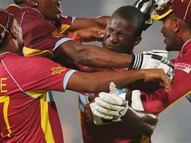 West Indies' players pounce on captain Darren Sammy, second right, to celebrate their win over Australia in the ICC Twenty20 Cricket World Cup match in Dhaka, Bangladesh. AP