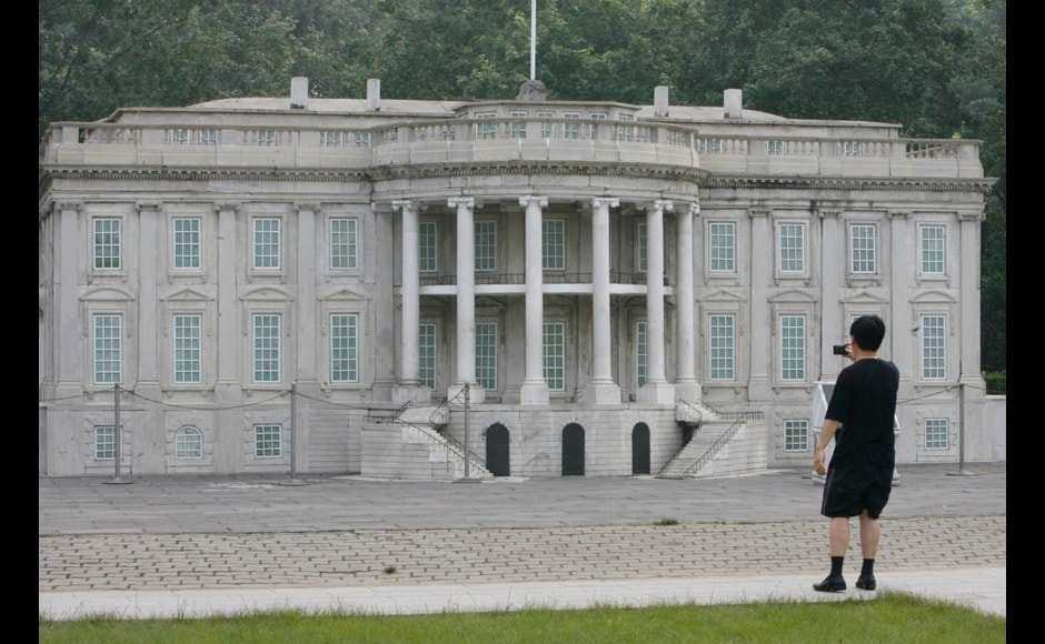 Visitor takes photographs of a replica of the White House at Beijing World Park