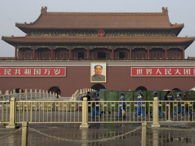 Cleaners walk past an area shielded by green nets in front of Tiananmen Gate in 2013. AP