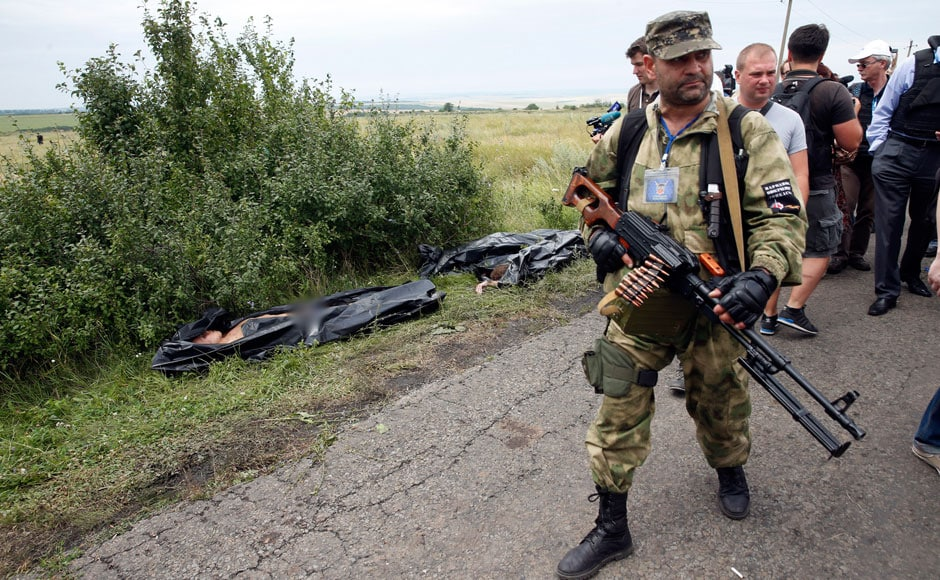 A pro-Russian separatist walks past bodies at the crash site of Malaysia Airlines Flight MH17. Cranes at the crash scene moved big chunks of the Boeing 777, drawing condemnation from Western leaders that the rebels were tampering with the site: Reuters